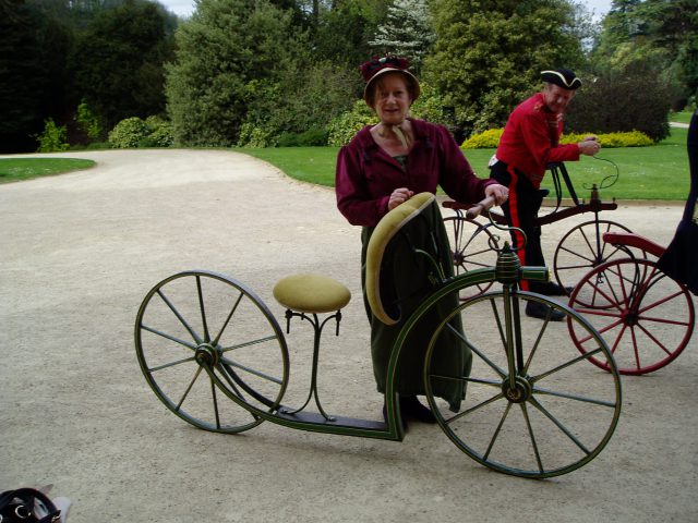 Lady in Regency dress next to a lady's velocipede