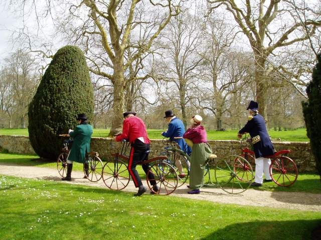 Men and women in Regency dress riding velocipedes on the grounds of Montacute House