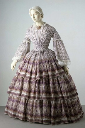 Dress with a pattern that complements the shape created by the cage crinoline worn underneath it. Museum no. T.702-1913